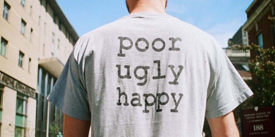Photograph of t-shirt reading 'Poor ugly happy'