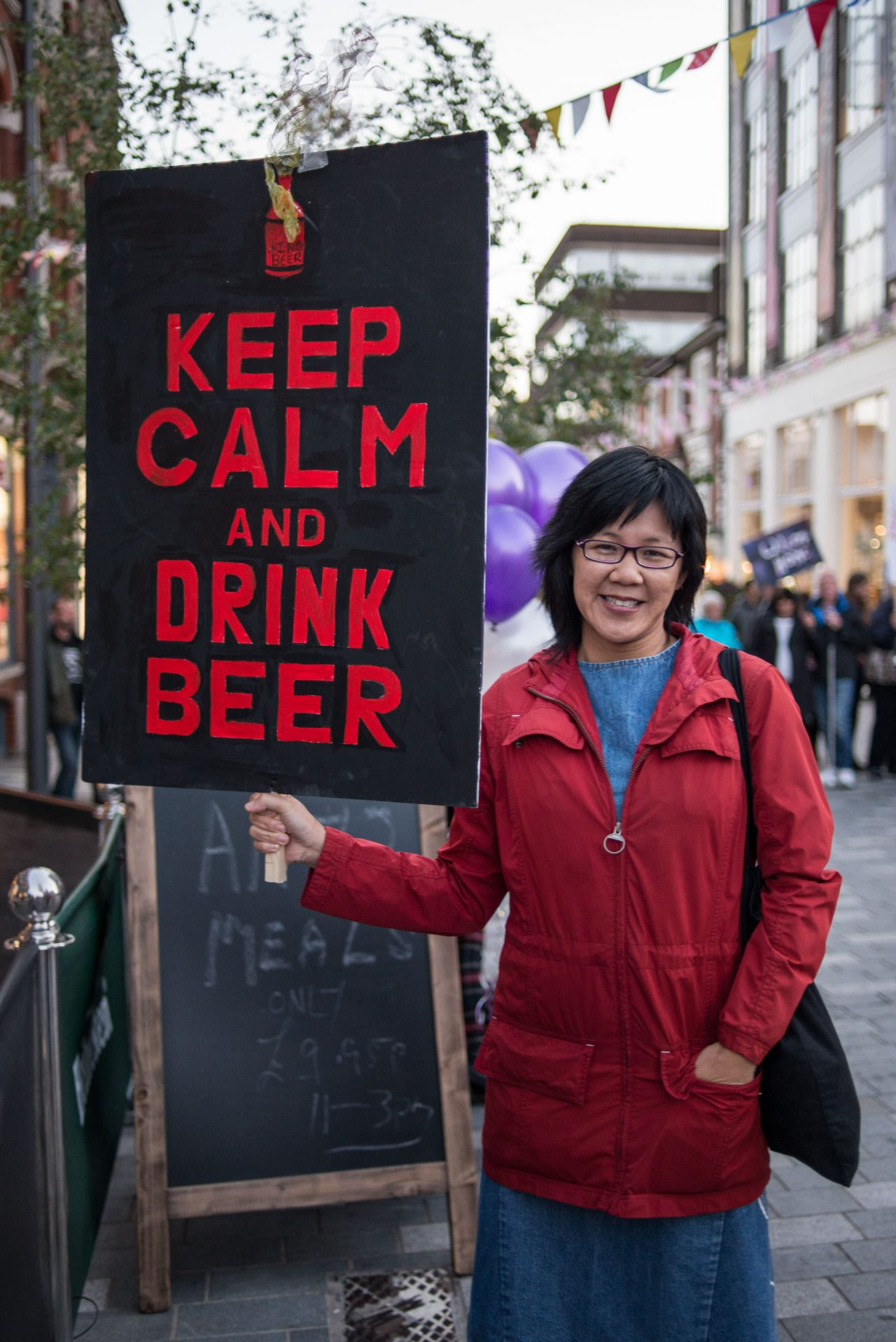 A smiling woman holding a placard that reads 'Keep Calm and Drink Beer' for Scott King's 'Keep The Home Fires Burning.'