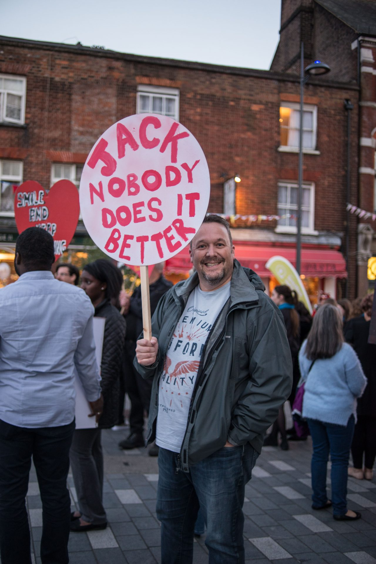 A man looking merry, holding a round placard saying 'Jack Nobody Does It Better' as part of Scott King's 'Keep The Home Fires Burning.'