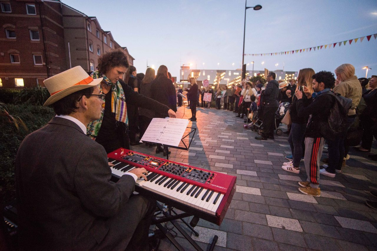 Keyboard player accompanies the choir who sing at dusk outside The Hat Factory at the launch of the public realm arts project.