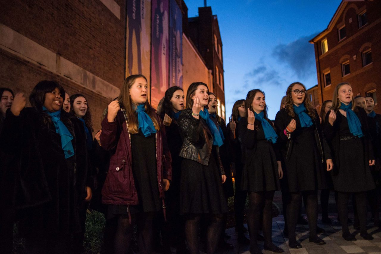 Choir wearing coats and blue scarves sing at dusk outside The Hat Factory at the launch of the public realm arts project.