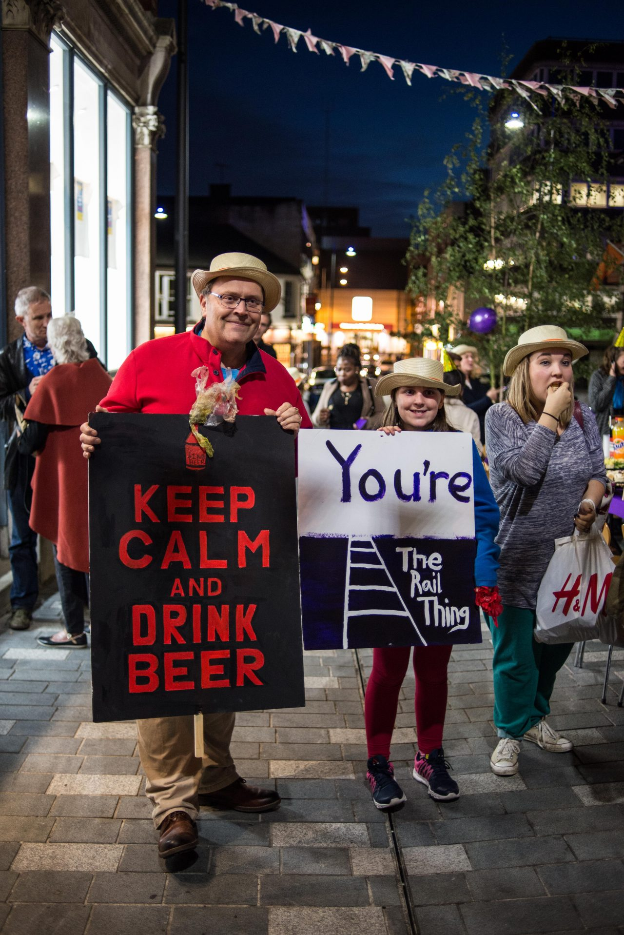 A father and his daughter wearing straw hats and carrying placards stating 'Keep Calm and Drink Beer' and 'You're The Rail Thing,' welcoming home commuters.