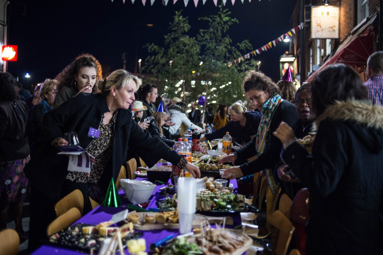 Residents of Luton enjoying the street feast launching the public realm arts project. Image shows people gathered around a purple table laden with nibbles.
