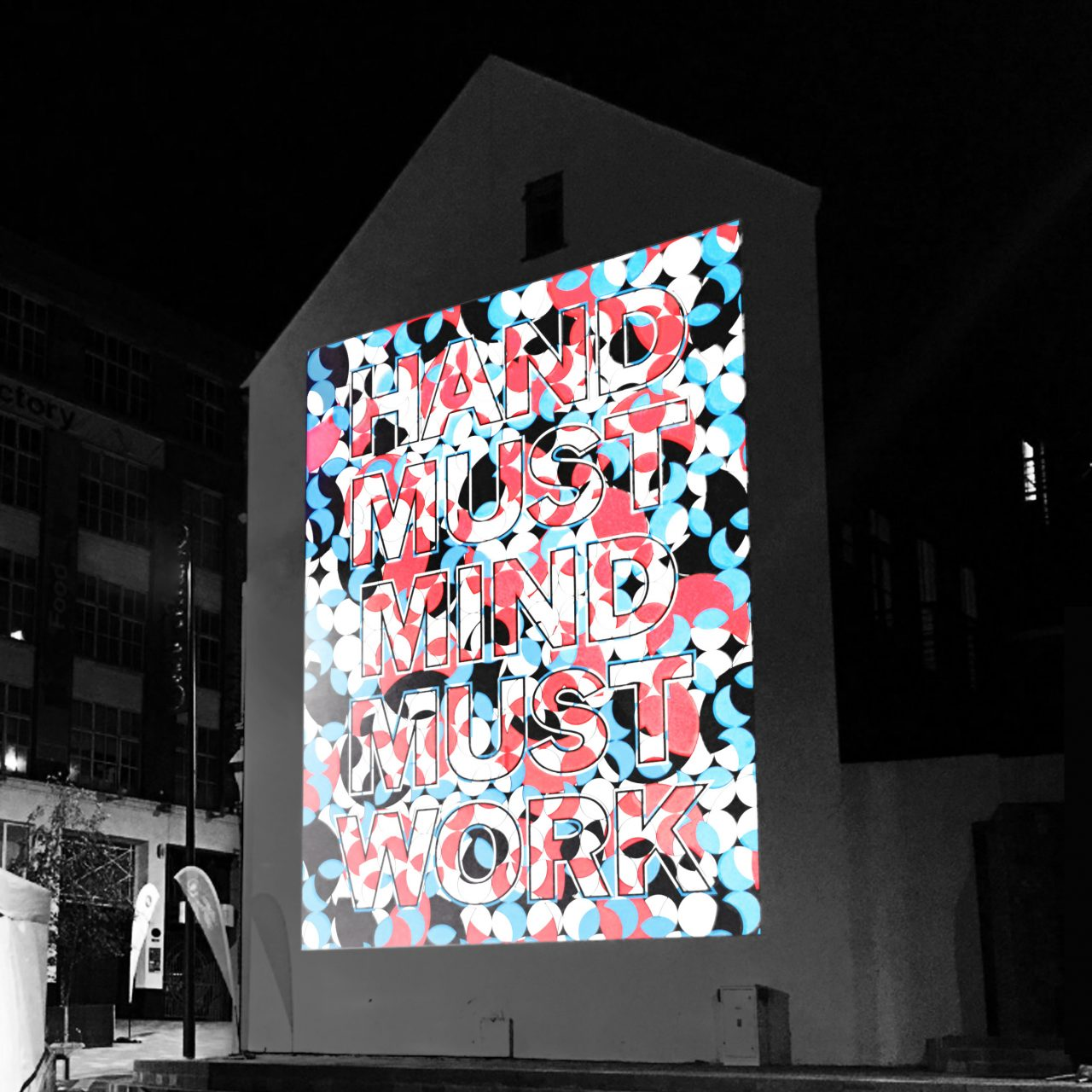 A brightly coloured projection of geometric shapes onto the Culture Wall at the launch of the public realm arts project with guests enjoying a feast next to it.