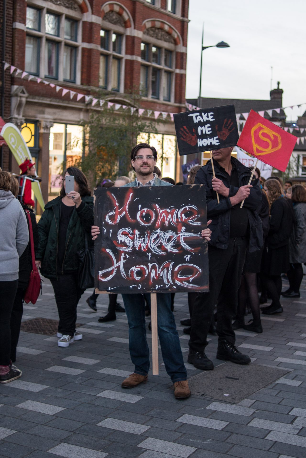 A man holding a placard that reads 'Home Sweet Home.'