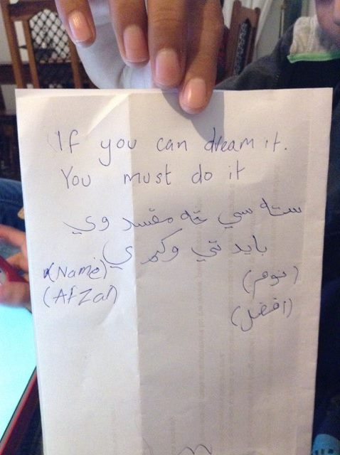 Pashto translation of 'If you can dream it, you must do it' on a piece of paper.
